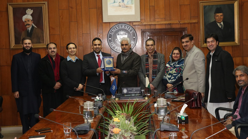 The Pro Vice Chancellor University of Peshawar flanked by three other public sector Universities' vice chancellors is offering souvenir to British Council delegation on 13th December, at committee room I.