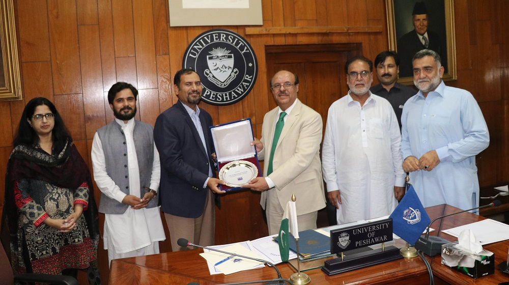 Rozan' Managing Director  Babar Bashir is presenting souvenir to University of Peshawar's Vice Chancellor  after a 'memorandum of understanding' signing ceremony with Social work department on 12th september,2019 to carry a baseline survey and volunteer activities.