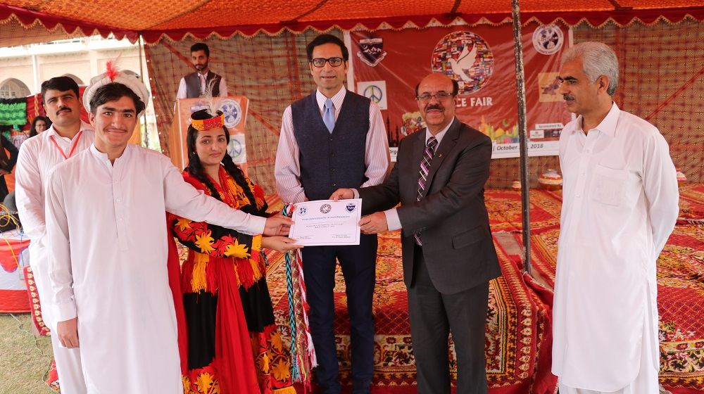 The Vice Chancellor University of Peshawar Prof. Dr. Muhamamd Asif Khan is giving away the best Stall prize to Kalashi group at the grand Peace Fair at academic block one being organised by the IRSA, UoP.