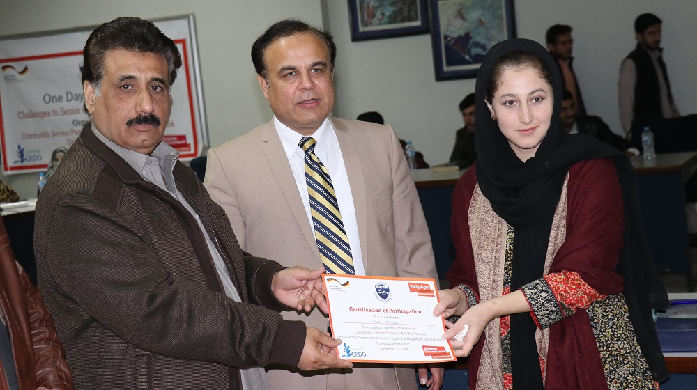 Registrar, University of Peshawar is handing over  a certificate of participation to a student  during one day conference at SSAQ auditorium under aegis of CSP and Help-age International  to promote  awareness on Senior Citizens legislation among youth as change agents on 20th December, 2018