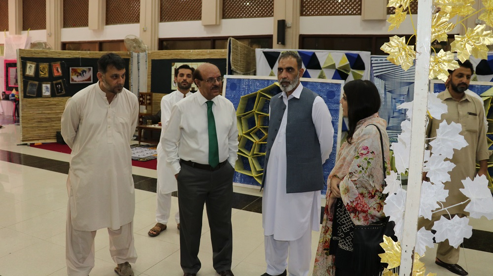The Vice Chancellor University of Peshawar Prof.Dr. Muhammad Asif Khan is inspecting the textile stalls projects while talking to a student during  BS thesis exhibition of Arts and Design on the 2nd of October, 2019 at TCC hall.