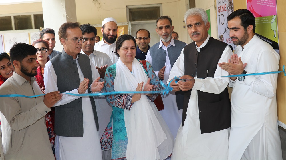 Pro-Vice Chancellor Prof. Dr. Johar Ali is cutting the blue ribbon ceremony at the one day poster  exhibition at department of Journalism and Mass Communication on 20th June, 2019 on Early Child marriages theme.