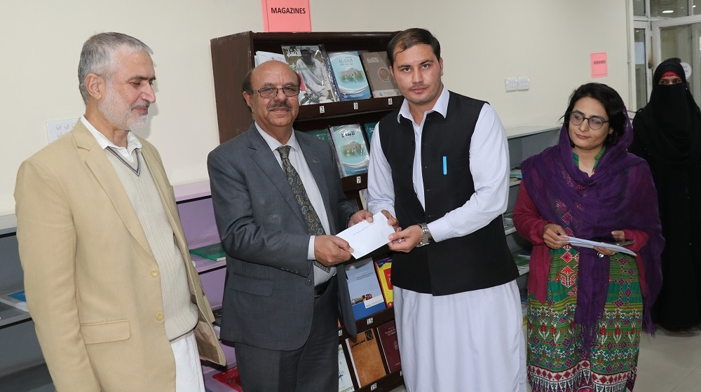 The Vice Chancellor University of Peshawar Prof.Dr.Muhammad Asif khan is handing over the cheque to the Archaeology student Haris Khan under Kohat Cement'CSR' through fund raising office efforts at the University on 9th December,2019.