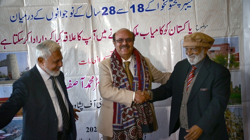 Vice Chancellor University of Peshawar Prof.Dr. Muhammad Asif Khan  after receiving the traditional 'Ajrak' from senior and veteran journalist Mehmud Shaam  is shaking hands at the prize distribution ceremony of National level Essay Competition for projecting cause for progressive Pakistan on 14th j