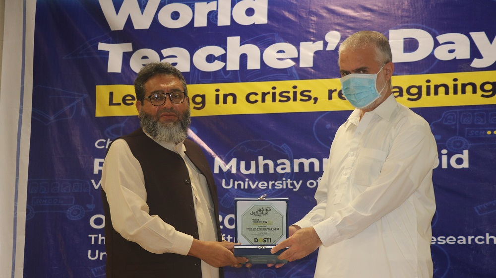 VC University of Peshawar Prof. Dr. Muhammad Abid recieves a shield from Director IER Prof. Dr. Muhammad Rauf while observing World Teacher's Day.